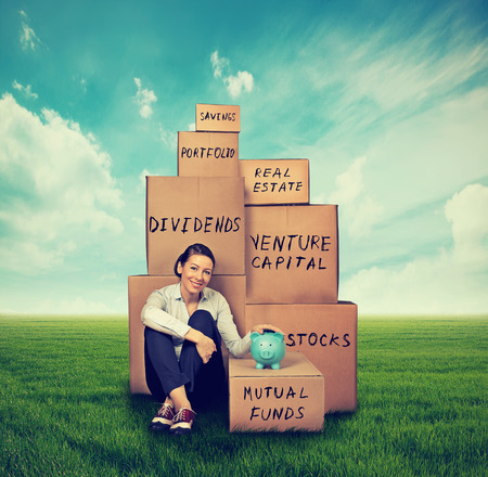 Successful young investor. Woman with piggy bank and boxes sitting outdoors on green grass Archivio Fotografico