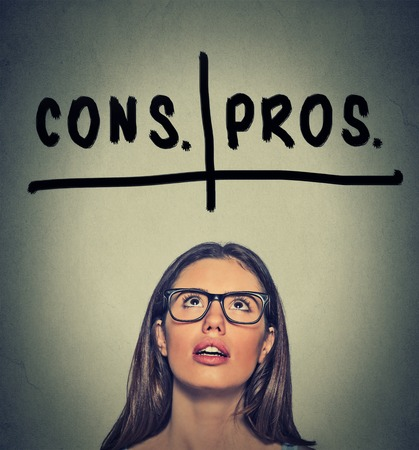 mindfulness: pros and cons, for and against argument concept. Young business woman with glasses looking up deciding isolated on gray wall background. Face expression, emotion, feeling, perception, vision, decision