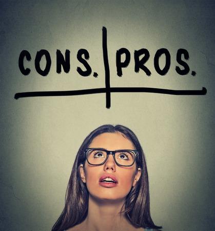 toma de decision: pros y contras, y en contra argumento concepto. Joven mujer de negocios con gafas mirando decisivo aislado sobre fondo gris de la pared. Expresi�n de la cara, emoci�n, sentimiento, percepci�n, visi�n, decisi�n Foto de archivo