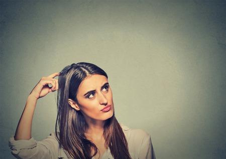Contused kobieta myślenia oszołomiony zarysowania głowę ma rozwiązanie samodzielnie na szarym tle ściany. Młoda kobieta, patrząc w górę