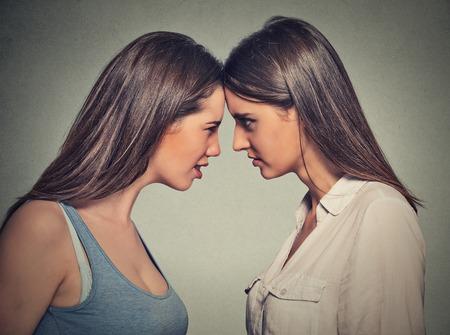amistad: Perfil lateral infelices jóvenes amigas que buscan el uno al otro la cabeza permanente para la cabeza en el fondo gris de la pared. Dificultades Amistad, problemas en el concepto de trabajo