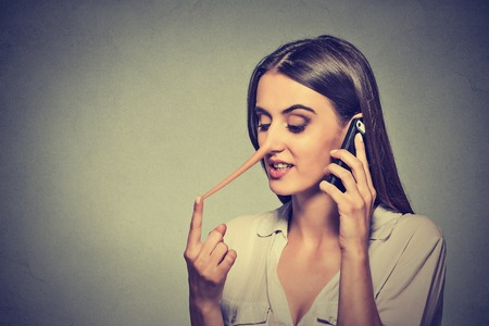 nariz: Retrato joven mujer hablando por teléfonos Telling Lies teléfono tiene una nariz larga aislada en el fondo gris de la pared Foto de archivo