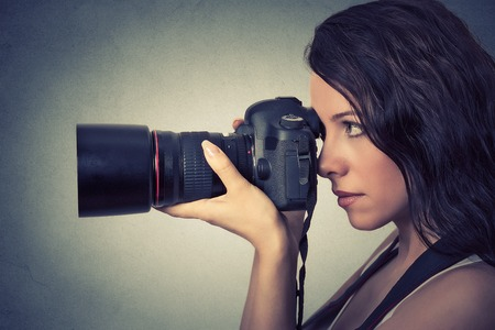 focus shot: Side profile young woman taking pictures with professional camera