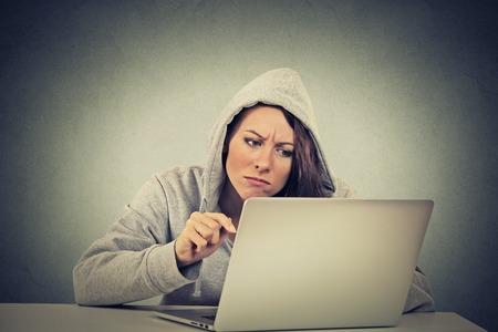 enojo: joven destacó mujer preocupada disgustado sentado delante de la computadora portátil sobre fondo gris de la pared. Negativos sentimientos emoción expresión cara percepción problema