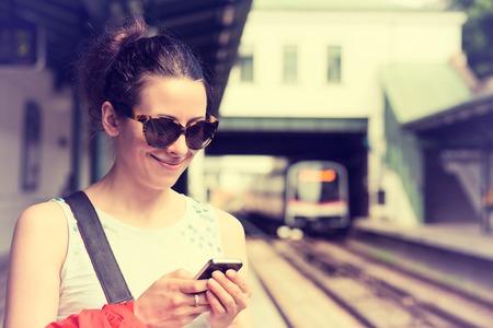 tren: Mujer joven que usa su teléfono celular en el andén del metro, la comprobación de mensajes de correo electrónico SMS o horario de trenes. Muchacha texting en el teléfono inteligente