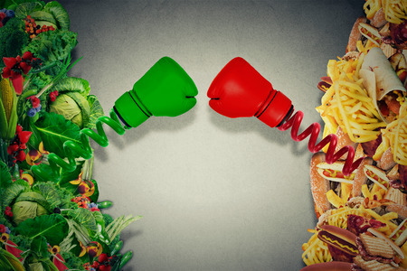 junk: Vegetarian food fighting unhealthy junk food with boxing gloves punching each other. Diet battle nutrition concept.