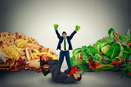 food fight: Vegetarian good food representative winner in a fight battle with unhealthy junk fatty food guy. Diet nutrition battle with boxing gloves concept idea. Healthy vs unhealthy option choice