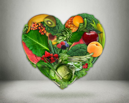 low fat diet: Healthy diet choice and heart health concept. Green vegetables and fruits shaped as heart  Heart disease prevention and food. Medical health care and nutrition dieting Stock Photo