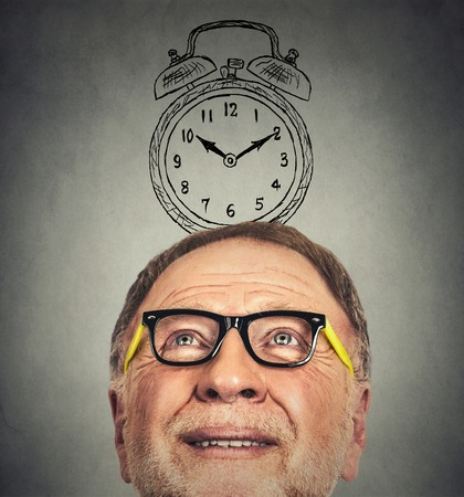 retirement happy man: Closeup portrait of senior man with glasses and alarm clock above his head looking up thinking isolated on gray wall background