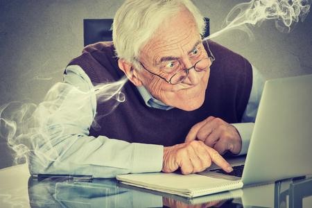 confundido: Estresado anciano ancianos utilizando equipo soplando vapor de los oídos. Frustrado hombre sentado a la mesa de trabajo en la computadora portátil aislada en el fondo de la pared gris. Gente mayor y concepto de la tecnología