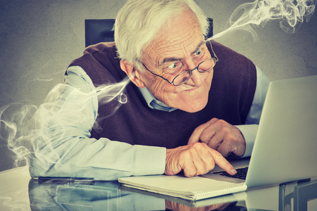 social problems: Stressed elderly old man using computer blowing steam from ears. Frustrated guy sitting at table working on laptop isolated on gray wall background. Senior people and technology concept