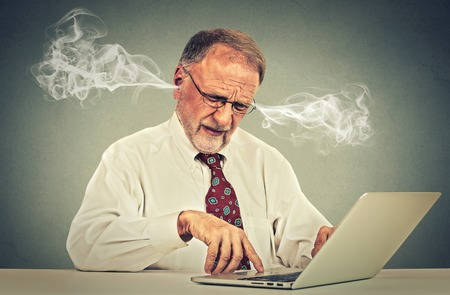 Stressed elderly old man using computer blowing steam from ears. Frustrated guy sitting at table working on laptop isolated on gray wall background. Senior people and technology concept