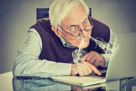 Stressed elderly man using computer blowing steam from nose frustrated sitting at table isolated on gray wall background. Senior people and technology concept Stock Photo