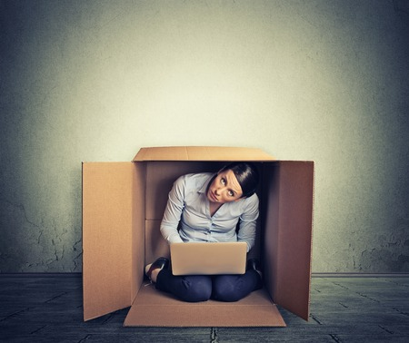 introvert: Businesswoman hiding in the box working on computer