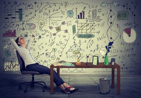 Mladý obchodní žena relaxaci u svého stolu ve své kanceláři