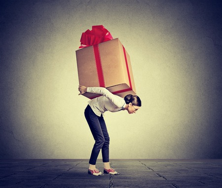 difficult task: Woman carrying a very big present on her back