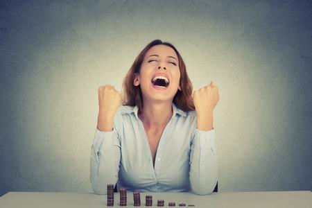 Jonge succesvolle zakenvrouw zitten aan tafel met een groeiende stapel munten viert schreeuwen vuisten gepompt. Financiële vrijheid doel succes concept Stockfoto