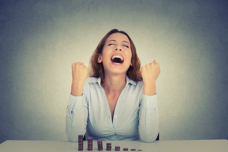 success: Joven mujer de negocios exitosa sentado a la mesa con una creciente pila de monedas celebra puños gritando bombea. La libertad financiera éxito objetivo concepto Foto de archivo