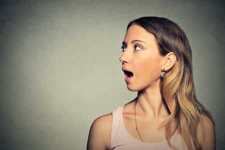 headshot: Closeup side view profile portrait woman talking with sound coming out of her open mouth isolated grey wall background. Human face expression emotions. Communication, information, intelligence concept