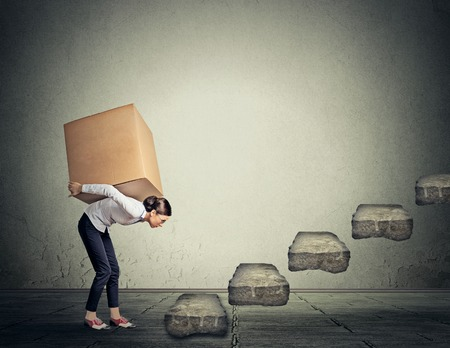 difficult task: Difficult task perspective concept. Young slim woman entrepreneur carrying large heavy box on her back upstairs Stock Photo