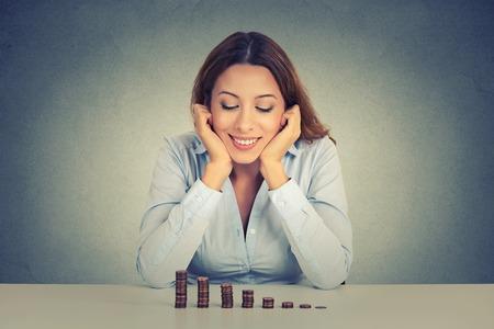 젊은 성공적인 비즈니스 여자 동전의 스택을 성장보고 테이블에 앉아. 금융 자유 대상 성공 개념