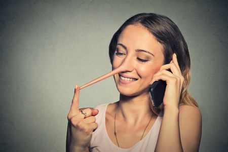 handphone: Young happy woman with long nose talking on mobile phone isolated on gray wall background. Liar concept. Human face expressions, emotions, feelings