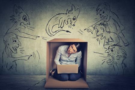 emociones: Hombres malos Malos apuntando a mujer estresada. Desesperada empresaria miedo escondido en una caja de trabajo sobre fondo gris pared de la oficina portátil. Emociones humanas negativas enfrentan sentimientos de expresión percepción vida