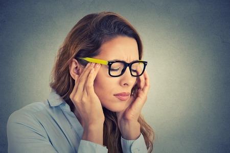 estrés: Retrato subrayó mujer de negocios joven que tiene dolor de cabeza Foto de archivo