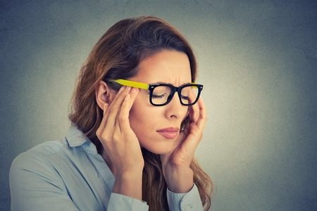 Portrait stressed young business woman having headache