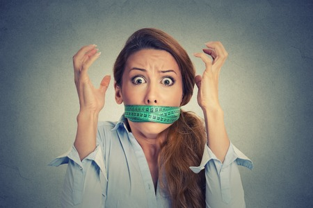 estrés: Restricción de la dieta y el concepto de estrés. Retrato de joven mujer frustrada con una cinta métrica verde alrededor de la boca aislado en el fondo gris de la pared. Emoción expresión facial