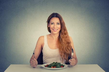free plate: Portrait of happy woman with plate of salad, against gray wall background Stock Photo