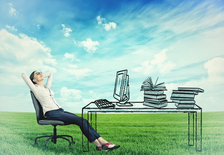 work life balance: young successful businesswoman relaxing sitting in the office at her desk in the middle of a green meadow. Stress free working environment concept