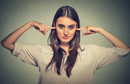 escuchar: Mujer que tapa los oídos con los dedos no quiere escuchar