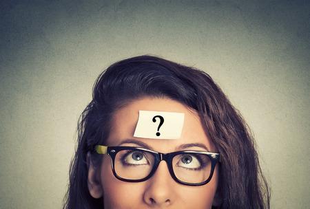 mente humana: Mujer que piensa con el signo de interrogación sobre fondo gris de la pared