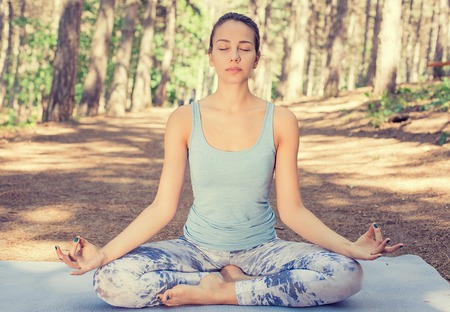 sitting meditation: Beautiful young woman meditating outdoors in spring summer park Stock Photo