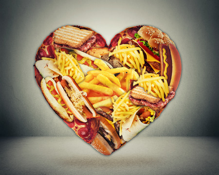 junks: Heart health and bad diet stroke risk concept. Heart shaped of fast junk fatty food Stock Photo