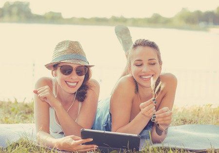 best friends girls: Two funny happy young women friends laughing browsing sharing watching social media videos blogs on pad computer laying outdoors on green meadow on sunny summer day Stock Photo