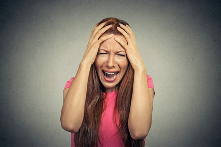 stupor: Closeup portrait stressed frustrated woman yelling screaming having temper tantrum isolated on gray wall background. Negative human emotion facial expression reaction attitude