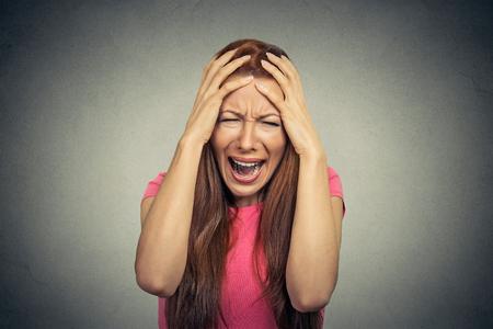 loco: Retrato del primer subrayó mujer frustrada gritando gritando tener rabieta aislado sobre fondo gris de la pared. Emoción humana actitud reacción expresión facial Negativo