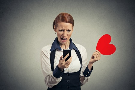 Portrait offended displeased young woman reading news on smart phone throwing away red heart isolated on gray wall background. Human facial expression emotion feeling reaction Banco de Imagens