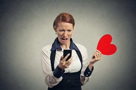 madre soltera: Retrato ofendido noticias disgustado lectura de la mujer joven en el teléfono inteligente tirar corazón rojo sobre fondo gris de la pared. Reacción facial humano sentimiento emoción expresión Foto de archivo