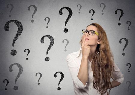 Denkende Geschäftsfrau mit Brille blickte auf viele Fragen Markierung auf grauen Wand Hintergrund isoliert Standard-Bild