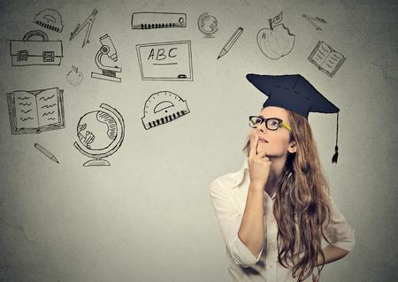 education: Belle jeune femme d'affaires avec l'obtention du diplôme chapeau regardant penser l'éducation isolé sur fond gris mur
