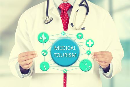 Close-up arts handen die witte kaart bord met medisch toerisme tekstbericht geïsoleerd op ziekenhuis kliniek kantoor achtergrond. Stockfoto