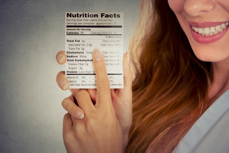 nutrition: Closeup cropped portrait image woman reading healthy food nutrition facts isolated on gray wall background Stock Photo