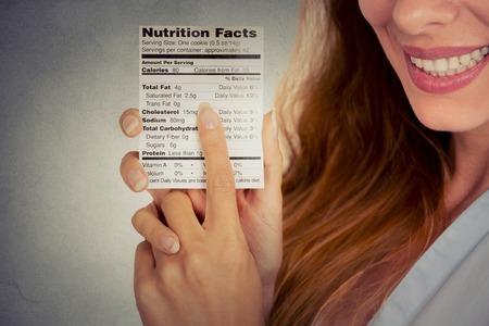 diabetes: Primer imagen Mujer retrato recortada de leer la información nutricional de alimentos saludables aisladas sobre fondo gris de la pared