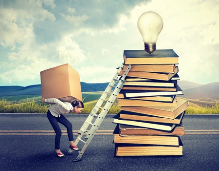 difficult task: Young woman with heavy box on her back climbing the stairs to the top of pile of books for new ideas information Stock Photo