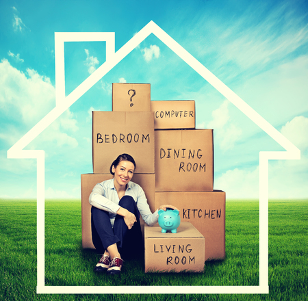 home expenses: young woman sitting on the green meadow with many boxes. Moving to a new place concept