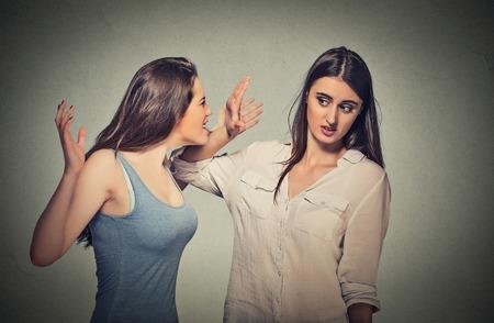 desconfianza: Chica condescendiente gritando señala el dedo en tímida mujer nerd tímida que está mirando hacia abajo