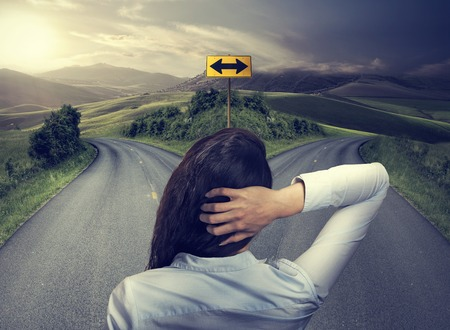 confusion: business woman in front of two roads thinking deciding hoping for best taking chance